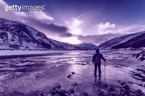 United Kingdom, Scotland, Highlands, female hiker standing at icy riverside - gettyimageskorea
