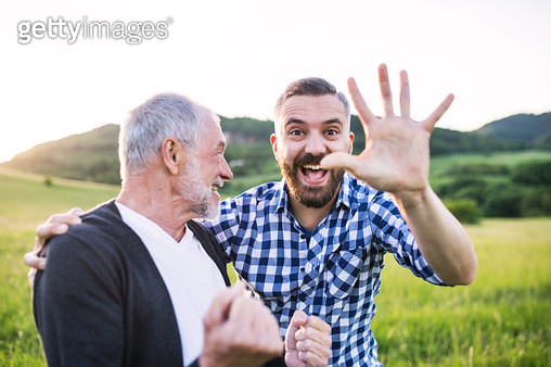 Father and adult son laughing and waving at camera - gettyimageskorea