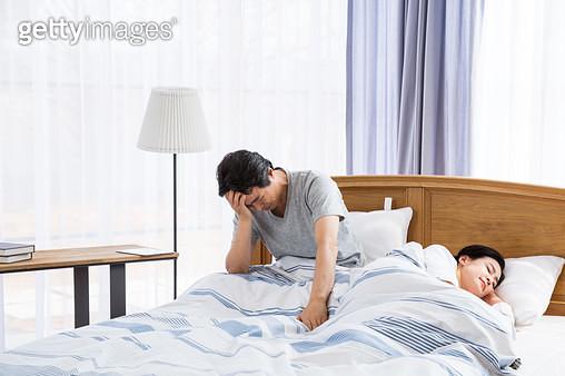 침대에 앉아 괴로워하는 중년남성 - gettyimageskorea