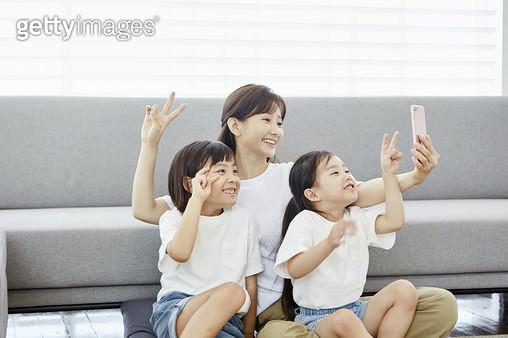 거실에서 휴대폰으로 사진촬영하는 엄마와 딸들 - gettyimageskorea