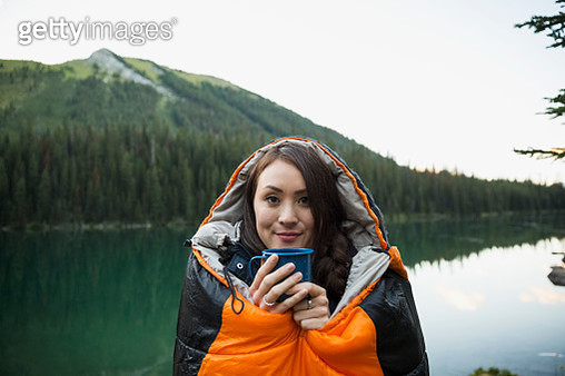Portrait smiling woman drinking coffee standing in sleeping bag at remote lakeside - gettyimageskorea
