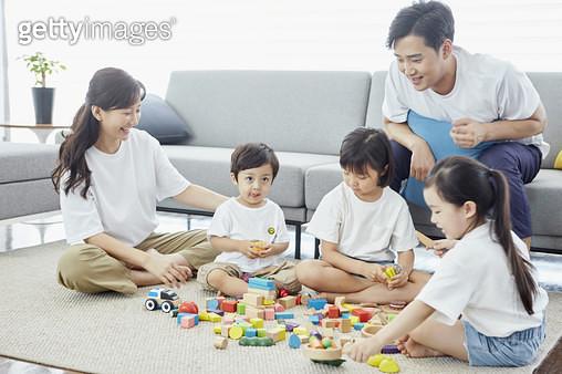 거실에서 블록을 가지고 함께 놀고있는 젊은가족 - gettyimageskorea