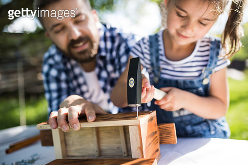 Father and little daughter hammering nails while building birdhouse - gettyimageskorea