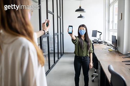 Women using covid-19 tracking app in office - gettyimageskorea