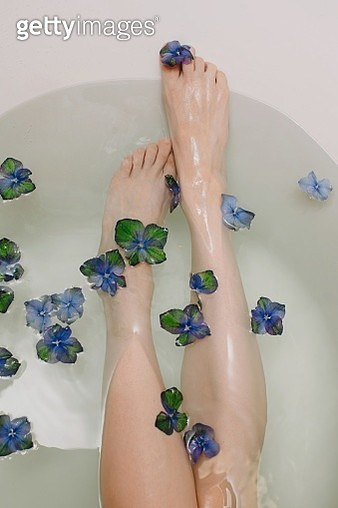 Womans leg in a bath with flowers - gettyimageskorea