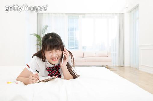 침대에 누워 통화하는 학생 - gettyimageskorea