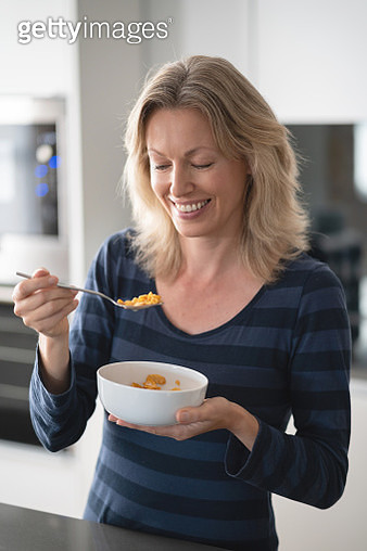 Happy woman at home eating a bowl of cereals for breakfast - gettyimageskorea