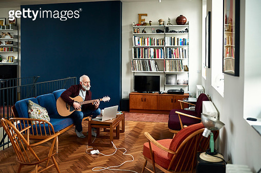 Man sitting on sofa and playing guitar, looking at laptop, creating music and learning to play - gettyimageskorea