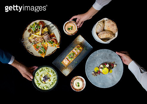 Three human hands placing food on a back table. - gettyimageskorea