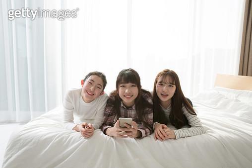 침대에서 스마트폰을 보며 웃는 여학생들 - gettyimageskorea