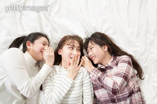 침대에 누워 속삭이는 여학생들 - gettyimageskorea