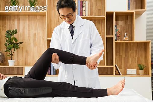 다리 치료를 하고 있는 의사 - gettyimageskorea