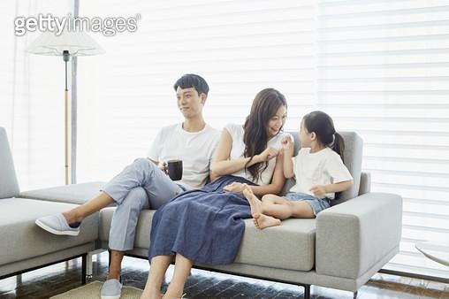 소파에 앉아있는 젊은가족 - gettyimageskorea