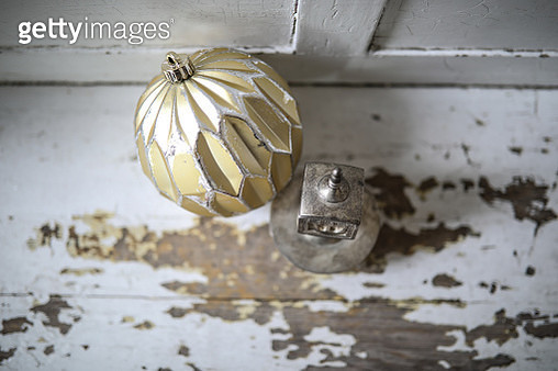 A Christmas ornament and a Hanukkah ornament sit side by side on a antique bench. They represent a home with both religions getting ready for the holidays of Christmas and Hanukkah. - gettyimageskorea