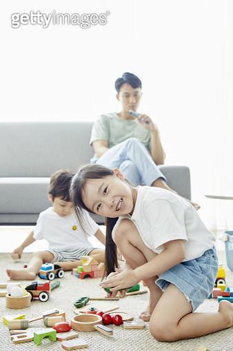 거실 바닥에 앉아 블록놀이를 하는 어린남동생과 카메라를 보며 웃는 누나 - gettyimageskorea