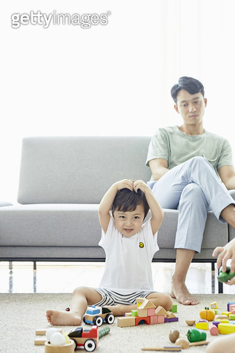 거실 바닥에 앉아 손으로 하트를 만드는 어린 남자아이 - gettyimageskorea