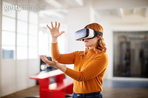 Young businesswoman using VR goggles and gesturing in office. Woman in casuals using virtual reality glasses in office. - gettyimageskorea