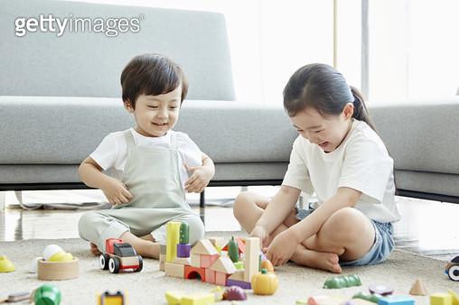 거실 바닥에 앉아 블록 놀이를 하는 누나와 어린남동생 - gettyimageskorea