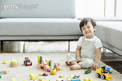 거실 바닥에 앉아 블록 놀이를 하는 어린남자아이 - gettyimageskorea