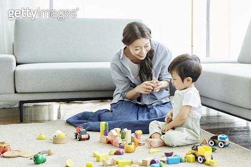 거실 바닥에 앉아 블록 놀이를 하는 엄마와 어린아들 - gettyimageskorea
