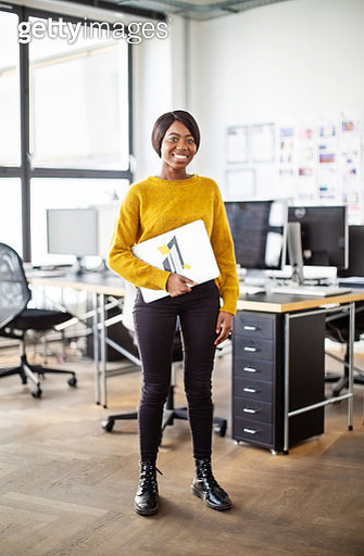 Full length portrait of happy young african businesswoman standing with a laptop in office. Female professional looking at camera and smiling. - gettyimageskorea