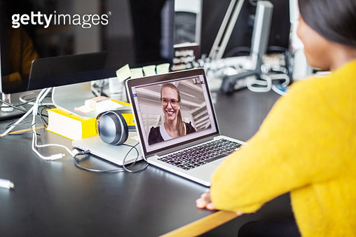 Two women having video conference at office. Female business professionals having a video call on laptop. - gettyimageskorea