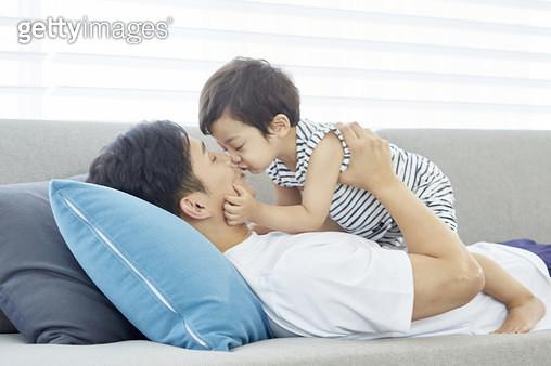 거실 소파에 누워있는 아빠 배에 앉아 아빠에게 뽀뽀하는 어린아들 - gettyimageskorea
