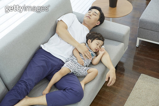거실 소파에 누워 낮잠자는 아빠와 어린아들 - gettyimageskorea