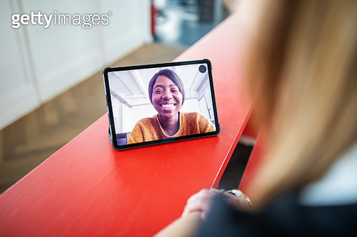 African woman talking with female colleague from a video call. Focus on digital tablet display. - gettyimageskorea