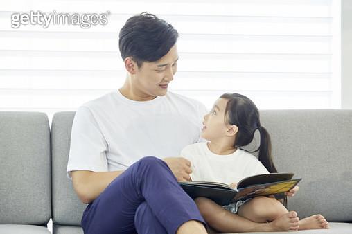 소파에 앉아 어린딸에게 동화책을 읽어주는 아빠 - gettyimageskorea