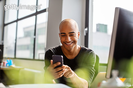 Smiling mid adult man using phone at his desk - gettyimageskorea