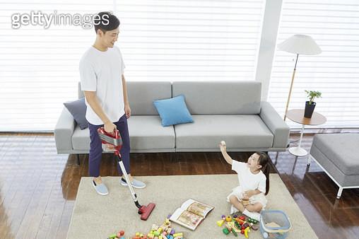 거실 바닥에 앉아 블록 놀이를 하는 어린딸과 청소기를 들고 서있는 아빠 - gettyimageskorea
