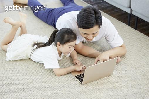 거실 바닥에 엎드려서 노트북을 보는 아빠와 어린딸 - gettyimageskorea