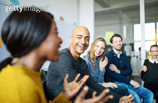 Business team smiling during a meeting - gettyimageskorea