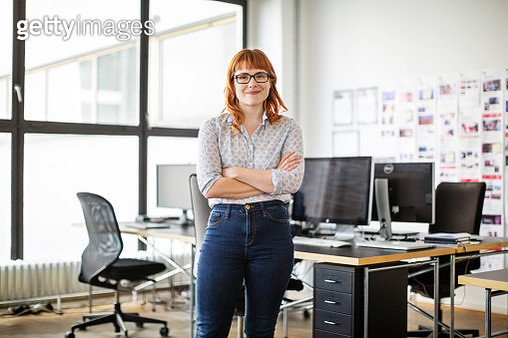 Portrait of confident young businesswoman standing with her arms crossed in office. Female professional in casual clothing looking at camera. - gettyimageskorea