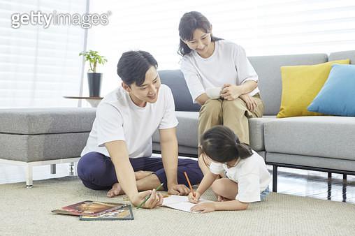 거실에서 엄마 아빠와 함께 그림그리는 어린딸 - gettyimageskorea