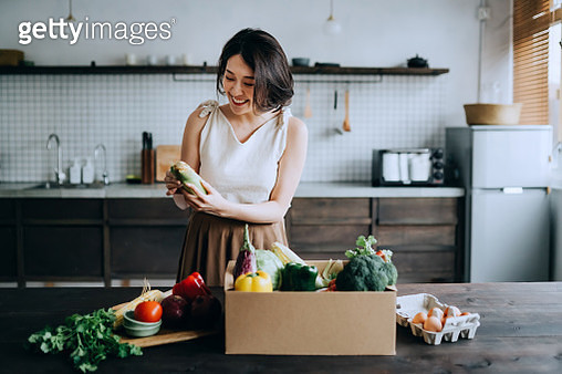 Beautiful smiling young Asian woman received a full box of colourful and fresh organic groceries ordered online by home doorstep delivery service. She is sorting out the groceries and preparing to cook a healthy meal - gettyimageskorea