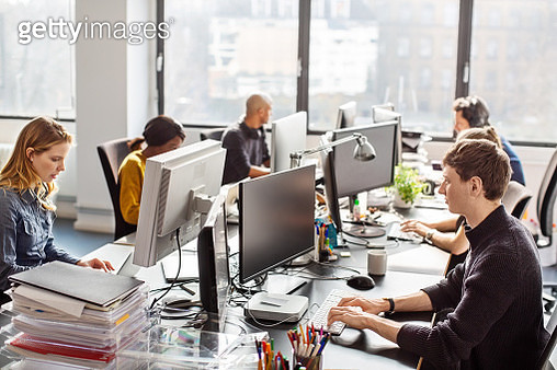 People working at a coworking desk in new office. Group of employees working in software development office. - gettyimageskorea