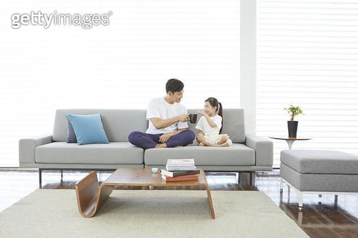 거실 소파에 앉아 있는 아빠와 어린딸 - gettyimageskorea