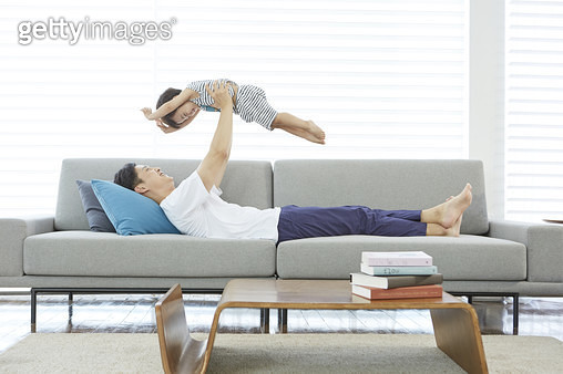 거실 소파에 누워 어린아들을 공중으로 들어 올리는 아빠 - gettyimageskorea