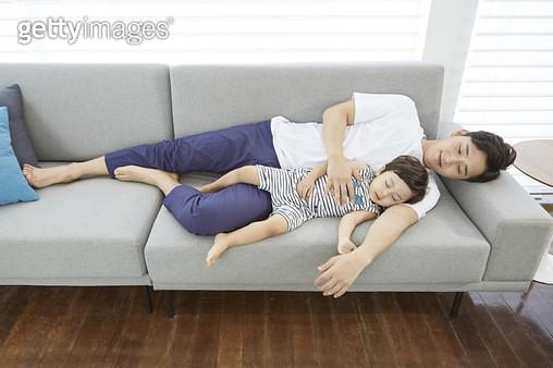 거실 소파에 누워 낮잠자는 어린아들을 바라보는 아빠 - gettyimageskorea