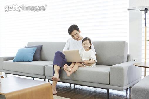 거실 소파에 앉아 어린딸과 함께 노트북을 보고있는 아빠 - gettyimageskorea