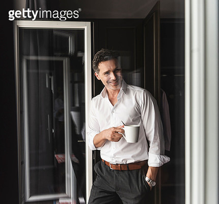 Smiling businessman with cup of coffee standing at the window at home - gettyimageskorea