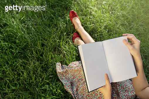 Low Section Of Woman Holding Book On Grassy Field - gettyimageskorea