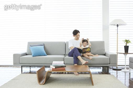 거실 소파에 앉아 어린딸에게 동화책을 읽어주는 아빠 - gettyimageskorea