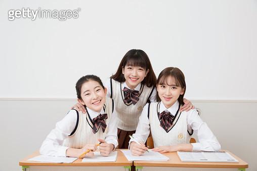 책상에 앉아 디바이스로 공부하는 여학생들 - gettyimageskorea