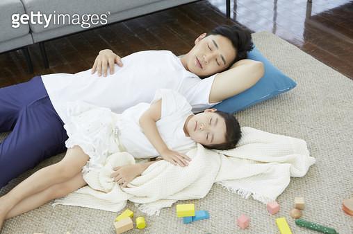 어질러진 거실 바닥에 누워 낮잠을 자는 아빠와 어린딸 - gettyimageskorea