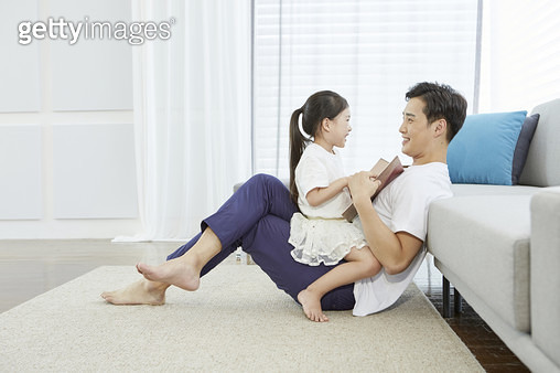 아빠와 마주보고 앉아 동화책을 보는 어린딸 - gettyimageskorea