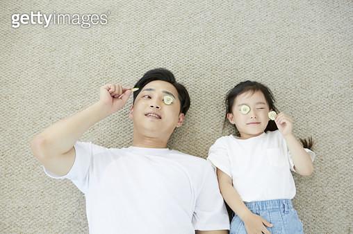 오이 조각으로 눈을 가리고 누워있는 아빠와 어린딸 - gettyimageskorea