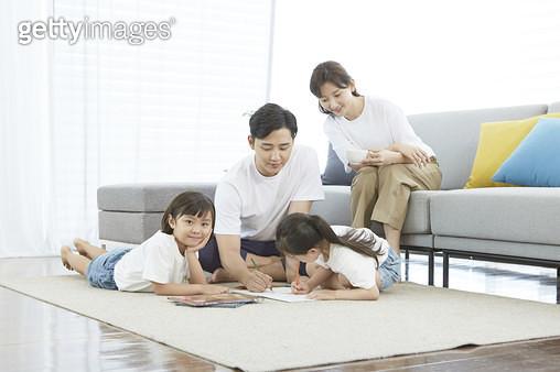 거실에서 즐겁게 놀고있는 젊은가족 - gettyimageskorea